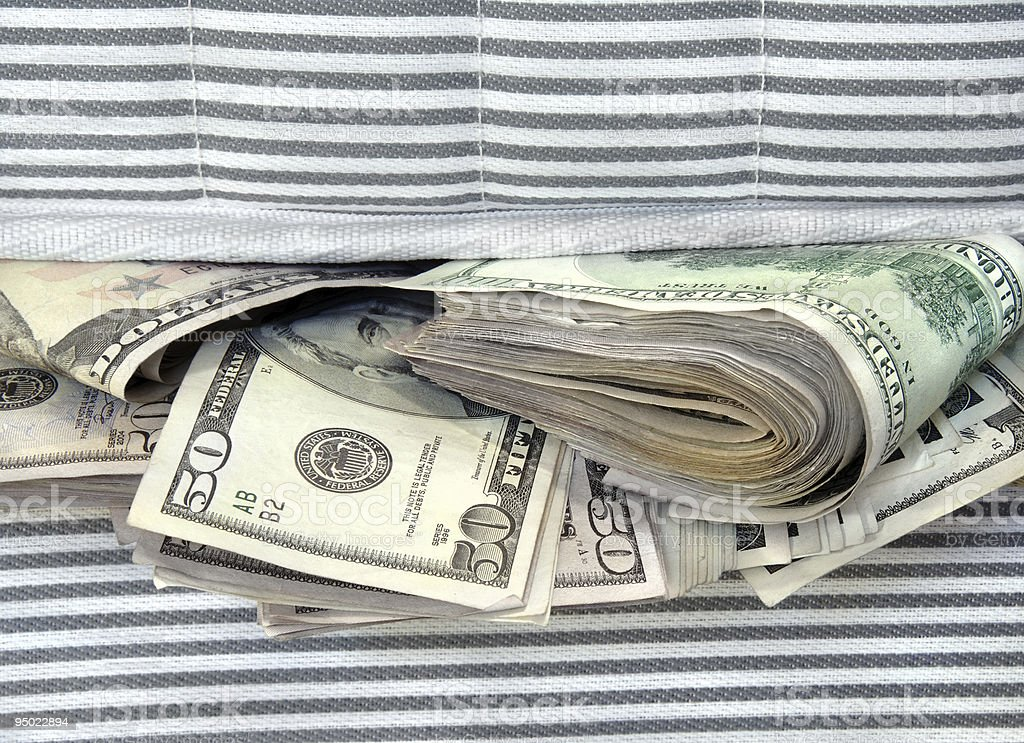 Money Stuffed in Between the Mattresses stock photo