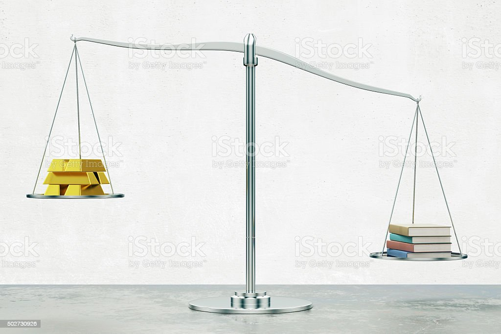 Money versus education concept with scales stock photo