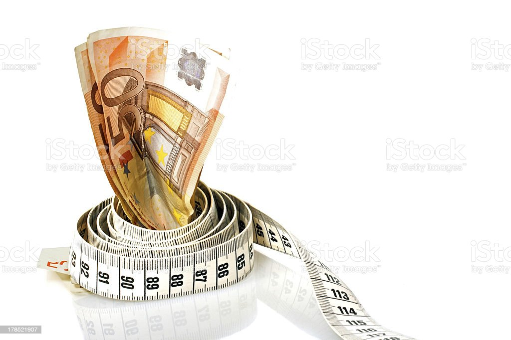 Money with a tape measure wrapped around it royalty-free stock photo