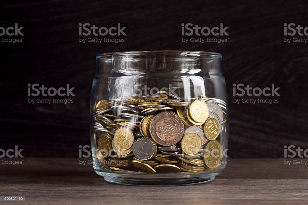 Moneybox with gold and silver coins on wooden background stock photo