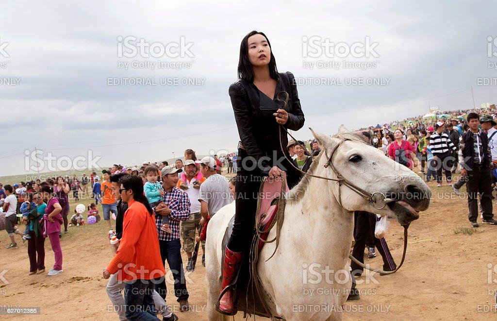 Mongol woman follows the horse races. stock photo
