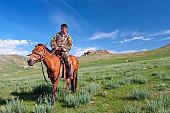Mongolian horseback rider posing with his horse