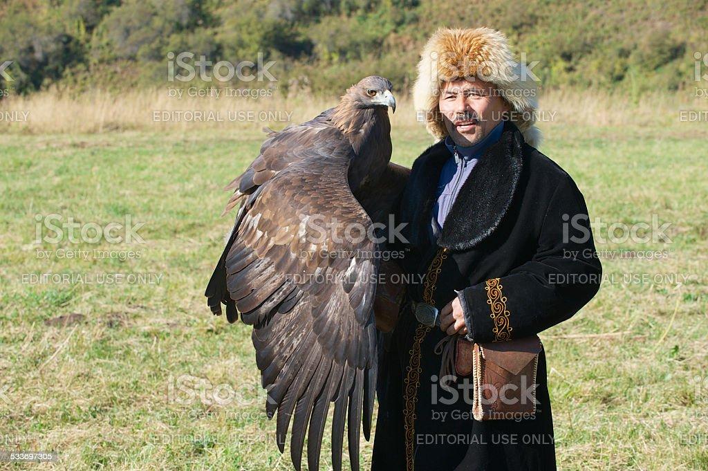Mongolian hunter holds golden eagle, circa Almaty, Kazakhstan. stock photo