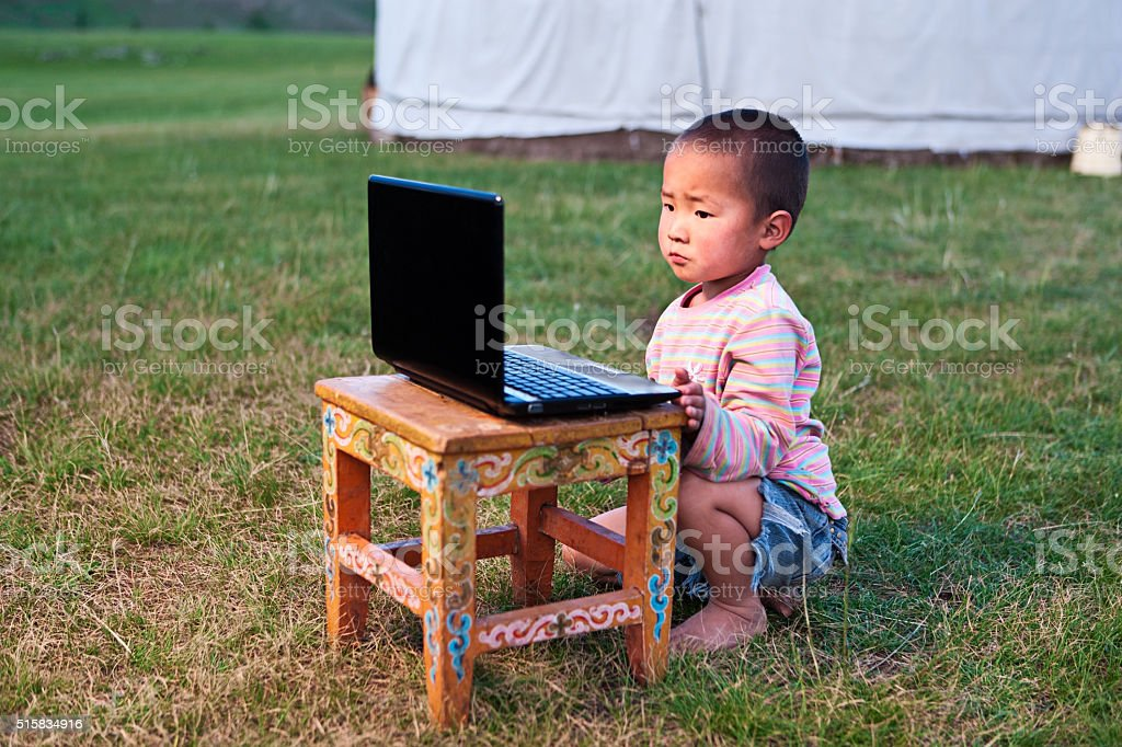 Mongolian little boy using laptop in front of ger stock photo