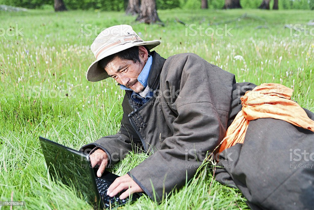 Mongolian man in national clothing using laptop royalty-free stock photo