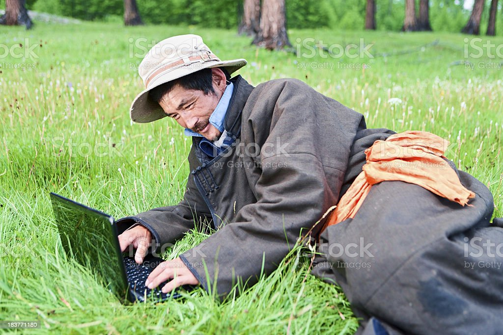 Mongolian man in national clothing using laptop royalty-free stock photo