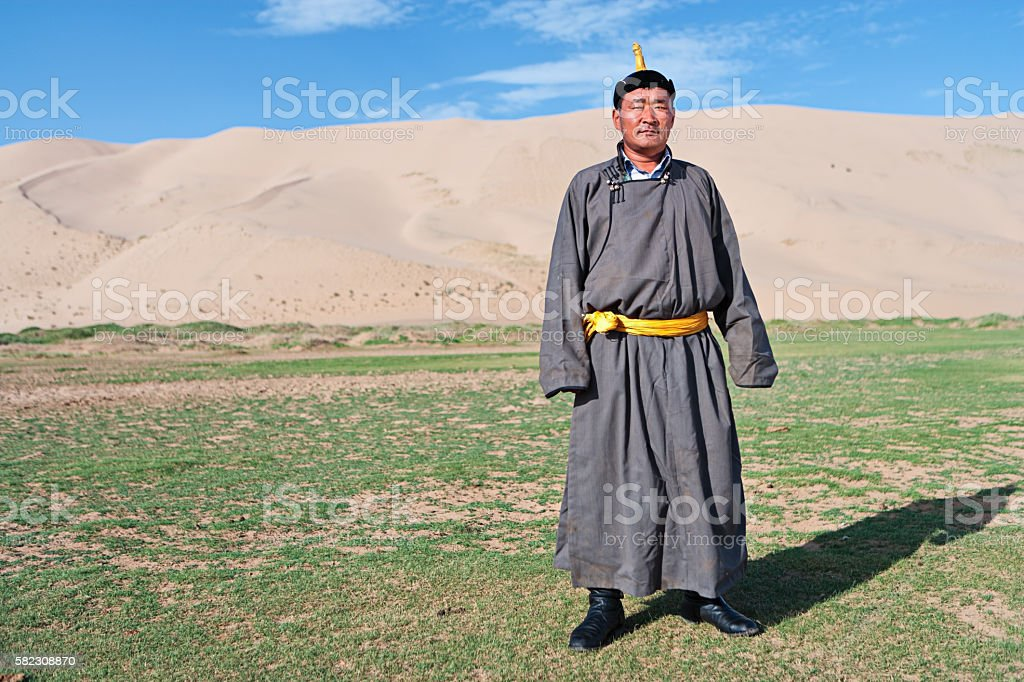 Mongolian man standing next to the sand dunes stock photo