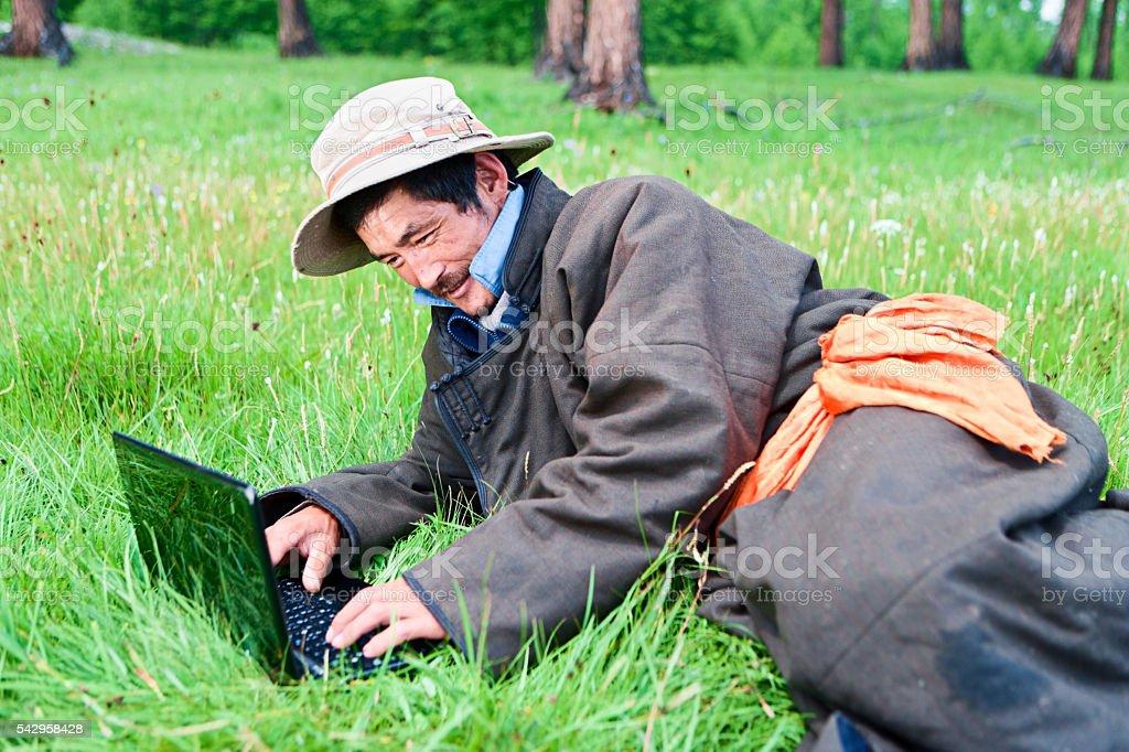 Mongolian man wearing national clothing using laptop stock photo