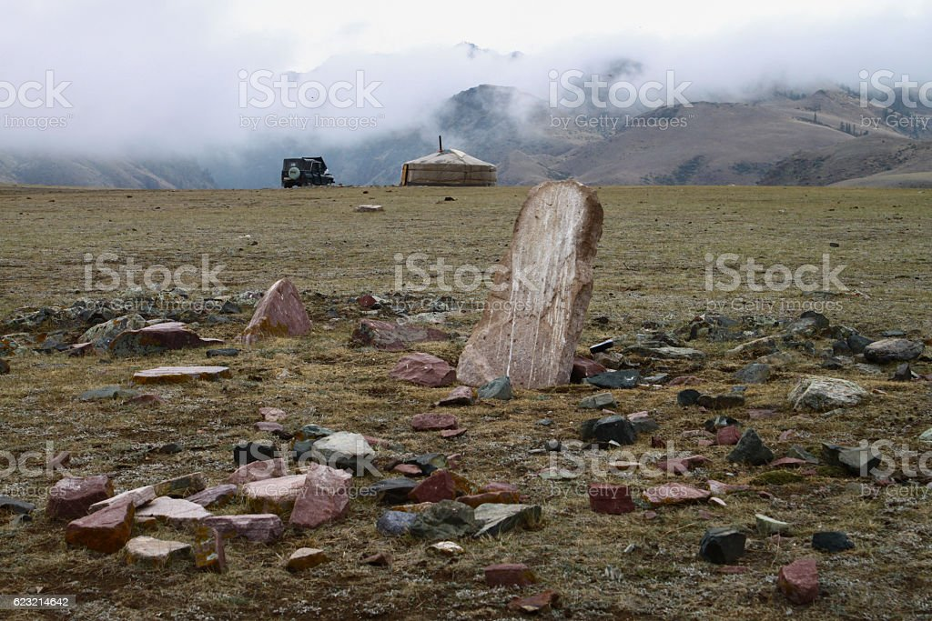Mongolian yurt in the mountains with anicent tomb stock photo