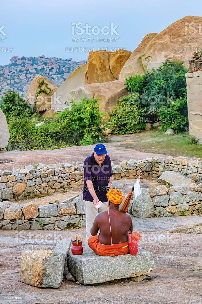 Monk asking for donation in Hampi, Karnataka, India. stock photo