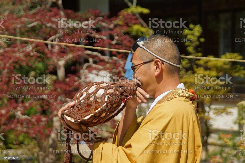 Monk blowing shell at Fire Walking Festival in Miyajima stock photo