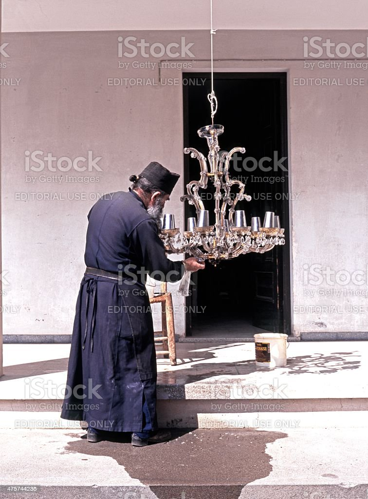 Monk cleaning a ceiling light, Cyprus. stock photo