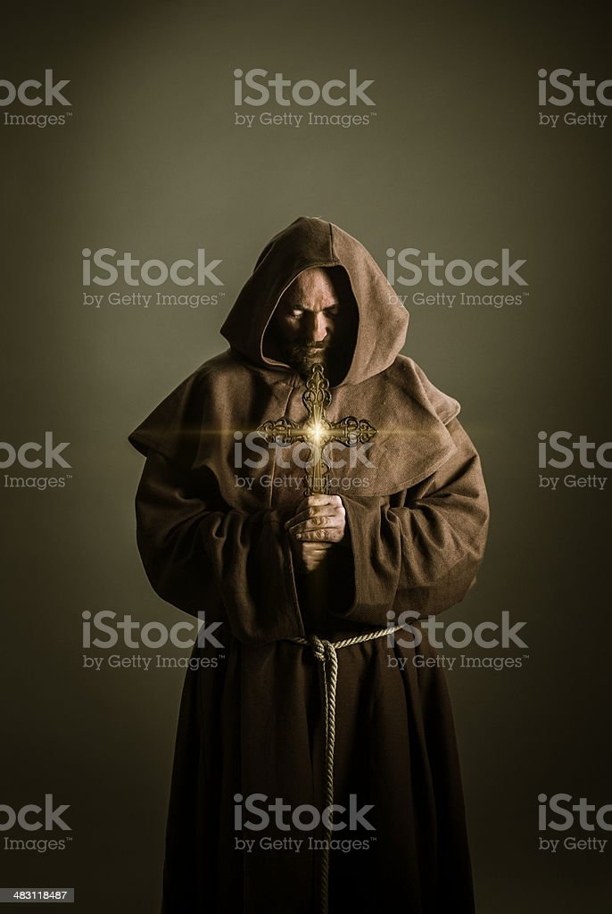 Monk holding cross stock photo