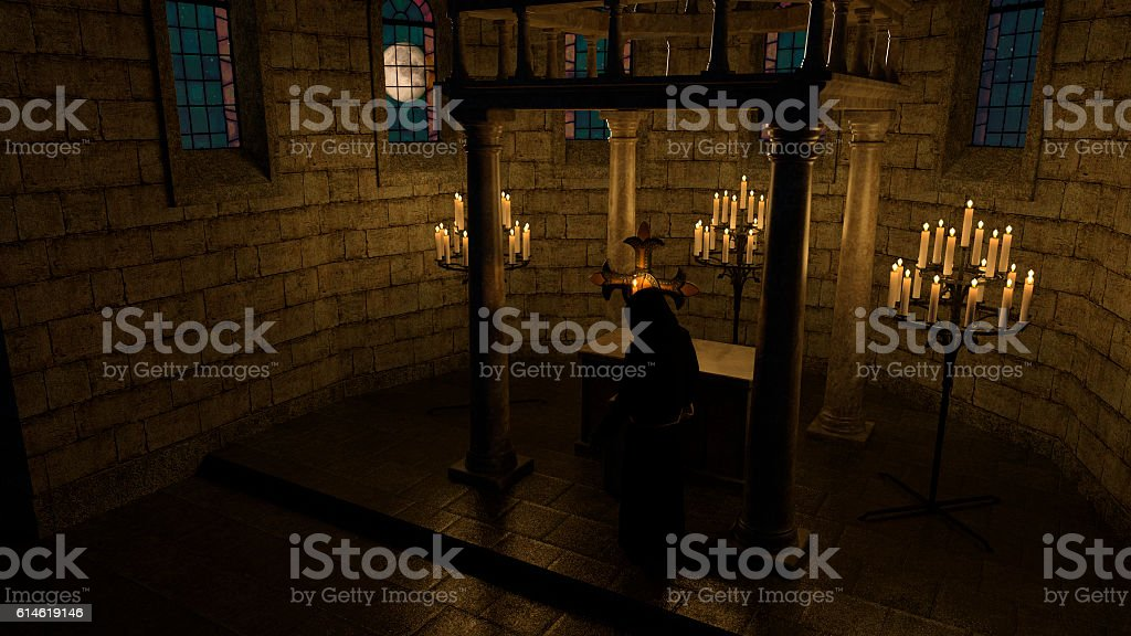Monk in front of the cross in the chapel stock photo