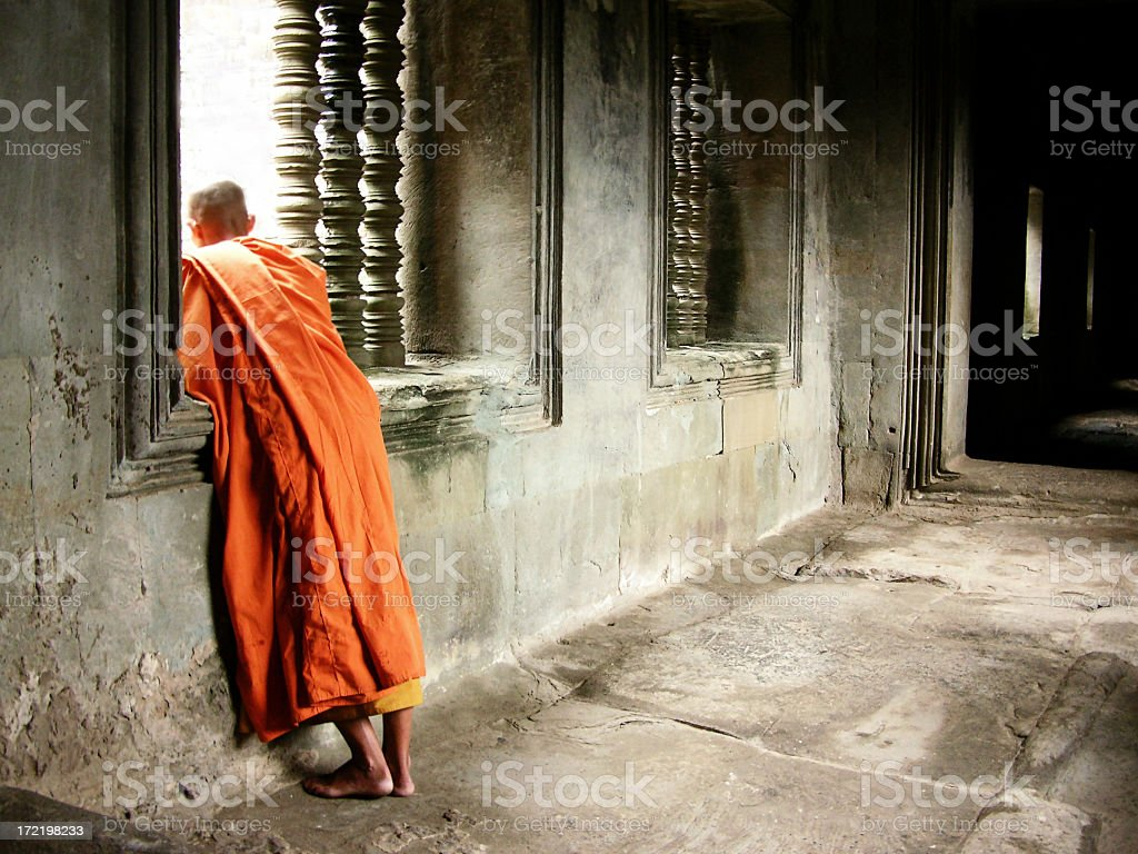 Monk in orange robe looking out window royalty-free stock photo