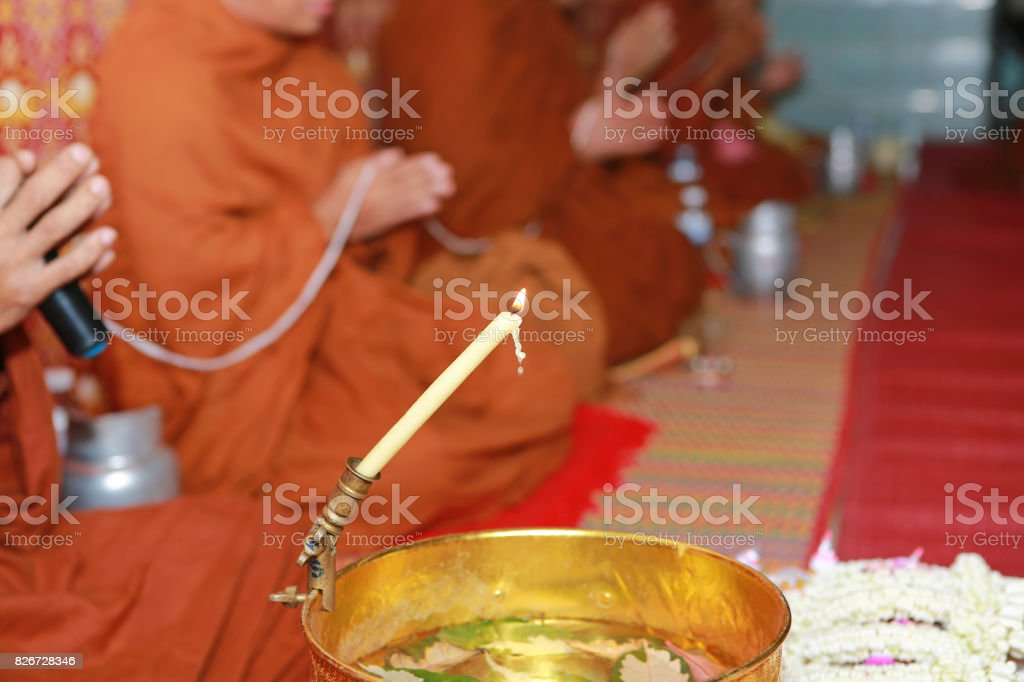 Monk makes holy water with candle in golden bowl. stock photo