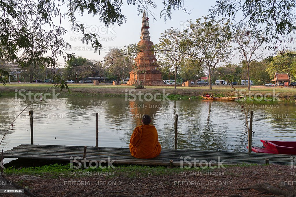 Monk meditating at Ayutthaya Historical park, Thailand. stock photo