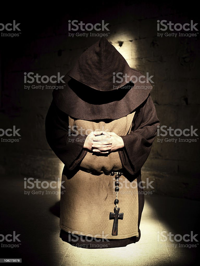 Monk Praying in the Shadows stock photo