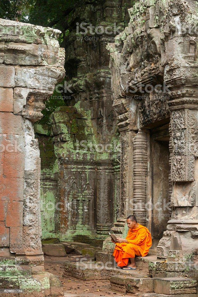 Monk reading at ruins stock photo
