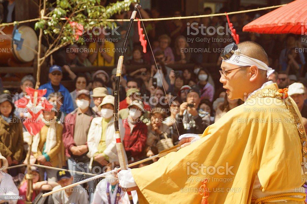 Monk shooting arrow at Fire Walking Festival in Miyajima stock photo