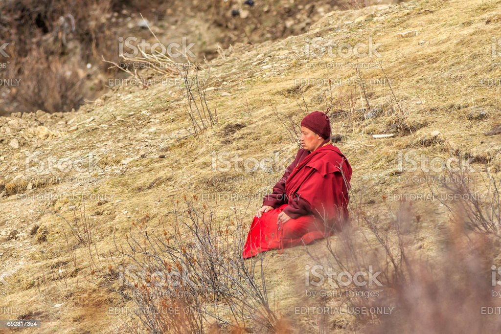 SICHUAN, CHINA - MAY 3 2016: Monk sitting praying on grasses in the mountain at Larung Gar(Larung Buddhist Academy). a famous Lamasery in Seda, Sichuan, China. stock photo