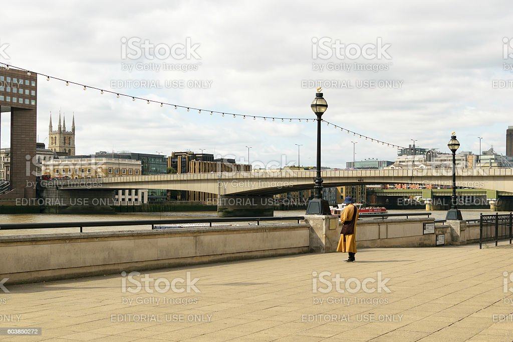 Monk stands on the bank of river Thames stock photo