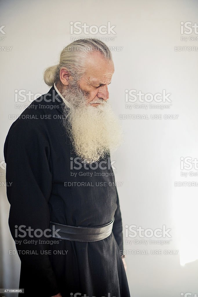 monk stays with closed eyes during Orthodox liturgy royalty-free stock photo