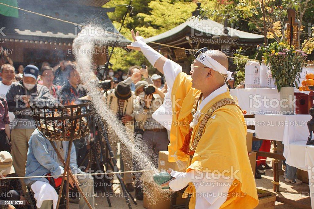 Monk throwing salt towards the fire stock photo