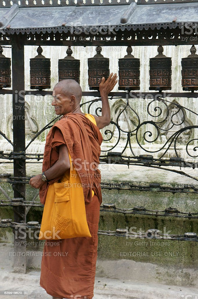 monk turning the prayer mills in buddhist temple Swayambhu stock photo