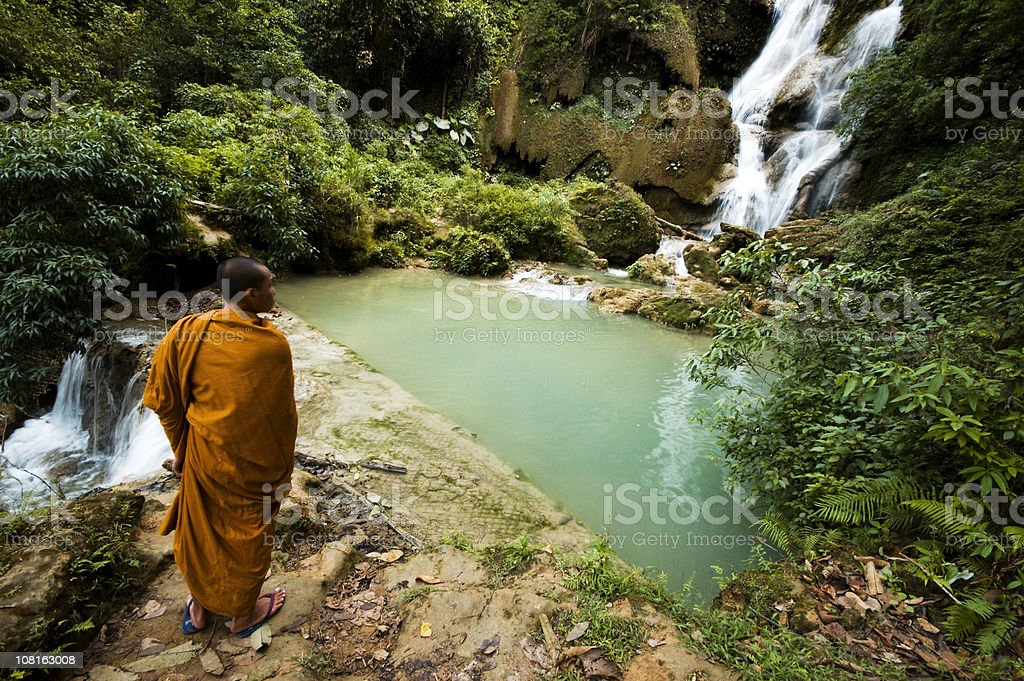 Monk Viewing Tat Kuang Si Waterfall in Laos stock photo