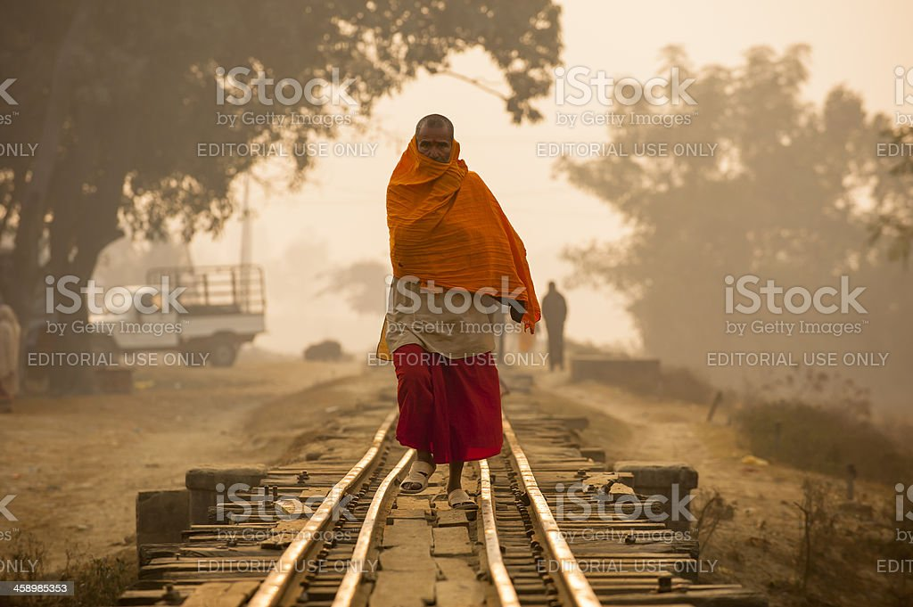 Monk walking on the railway in misty morning stock photo