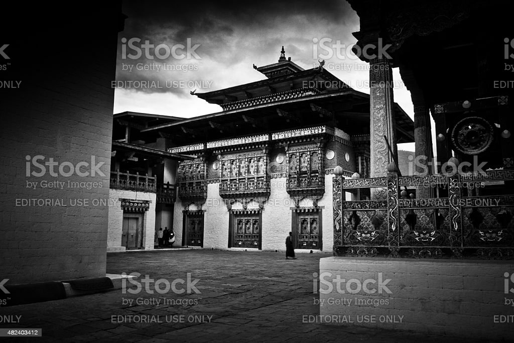 Monk walks the courtyard of Punakha Fortress Monastery, Paro, Bhutan stock photo