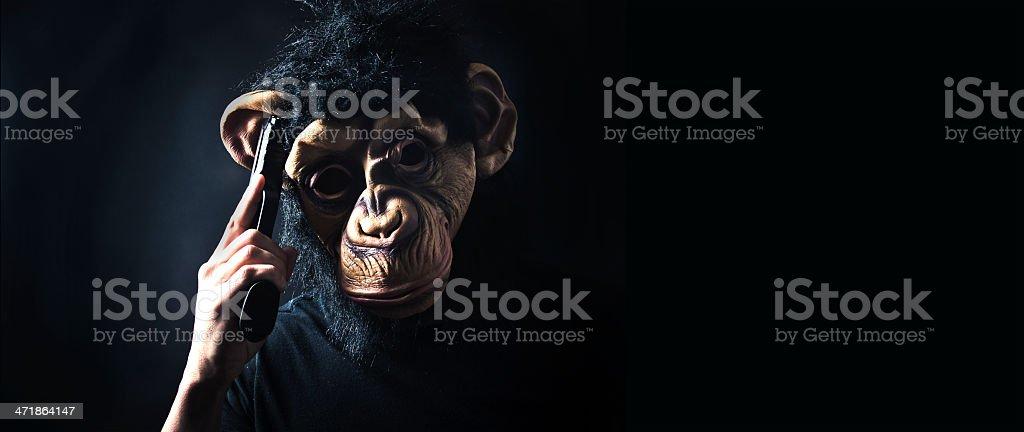 Monkey man robber holding a gun royalty-free stock photo