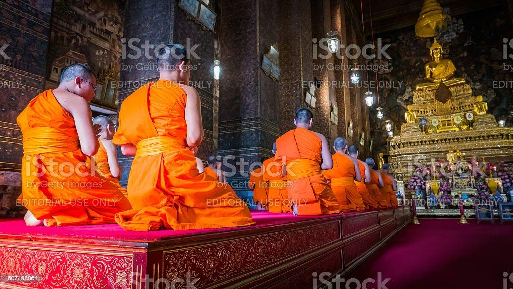 Monks praying at golden Buddha statue. stock photo