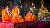 Monks praying at golden Buddha statue.