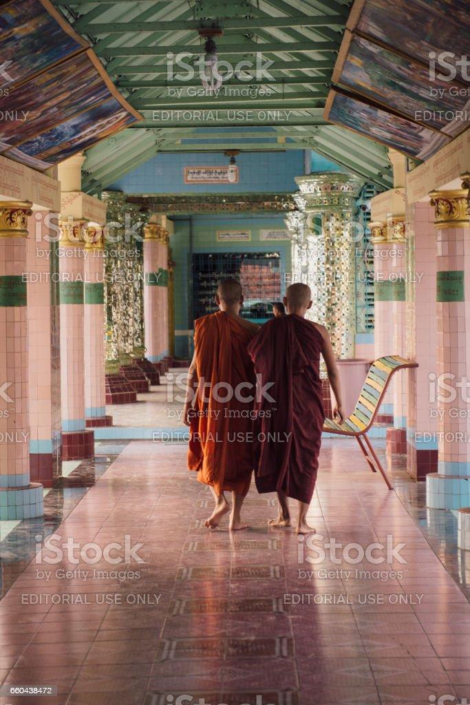 Monks walking inside Buddhist monastery stock photo