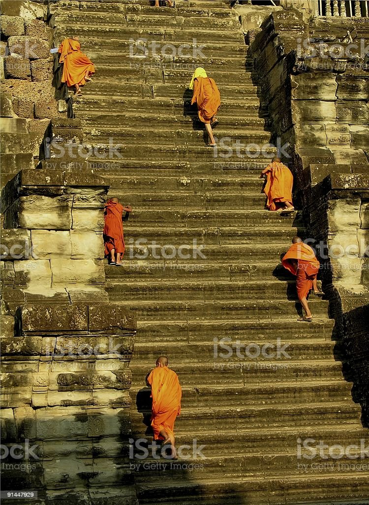 Monks walking upstairs in Angkor royalty-free stock photo