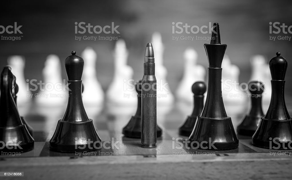 Monochrome closeup shot of bullet in row of chess pieces stock photo