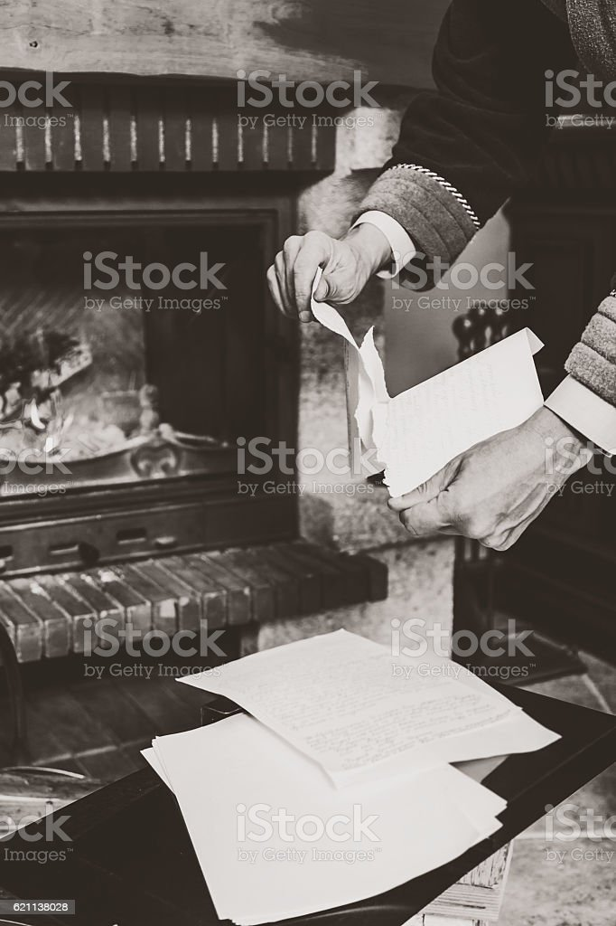 Monochrome image. Hands tear sheets in front of burning fireplace stock photo
