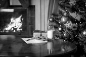 Monochrome image of letter and cookies for Santa on table