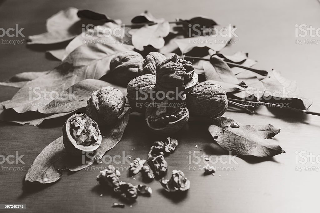 Monochrome image. Several walnut kernels and lie on wood background stock photo