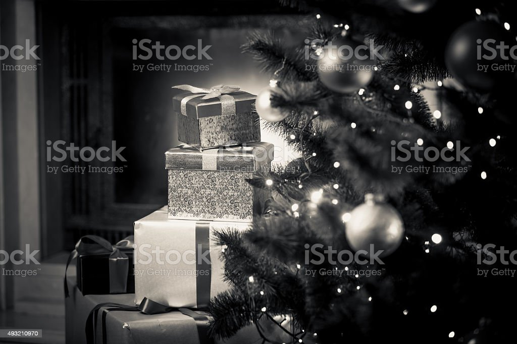 monochrome photo of Christmas gifts on floor stock photo