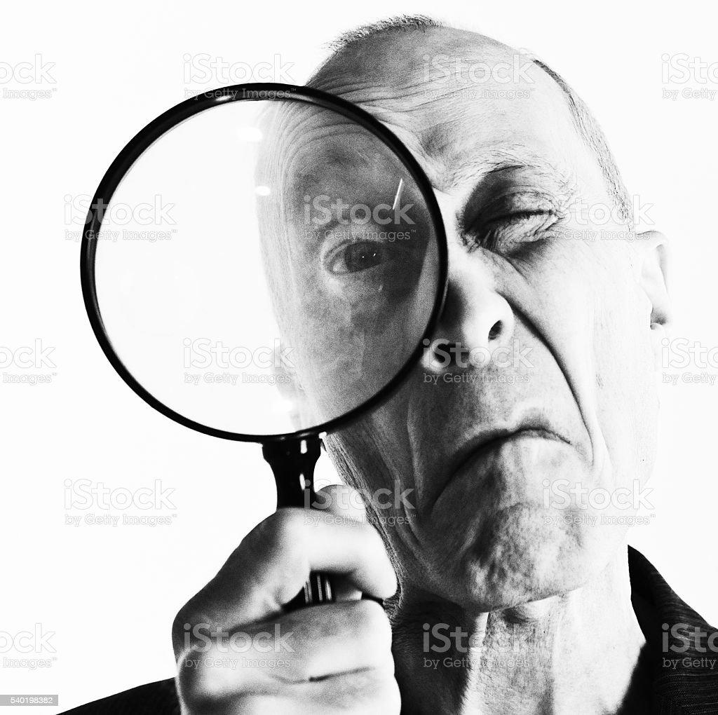 Monochrome portrait of senior man peering through magnifying glass, grimacing stock photo
