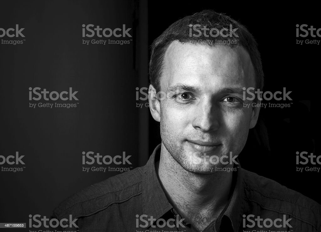 Monochrome portrait of young smiling Caucasian man on black back stock photo