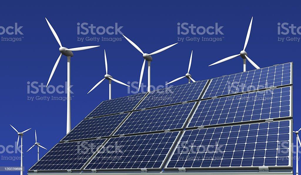 Monokristalline Solarmodule und Windkraftr?der vor blauem Hintergrund stock photo