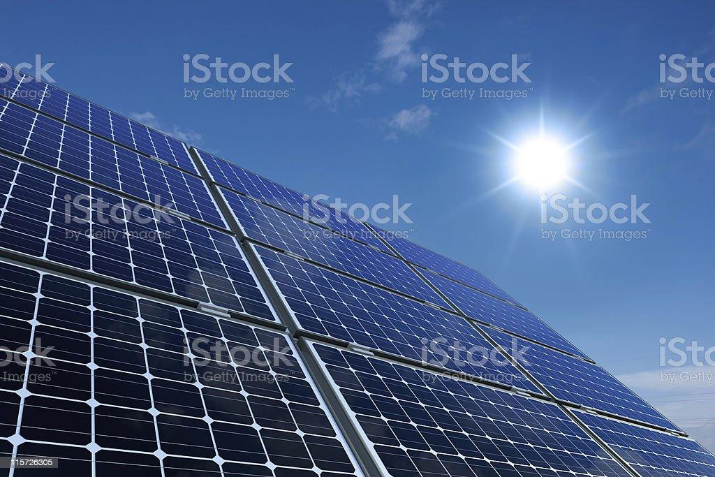 Monocrystalline solar panels glisten in the sun stock photo