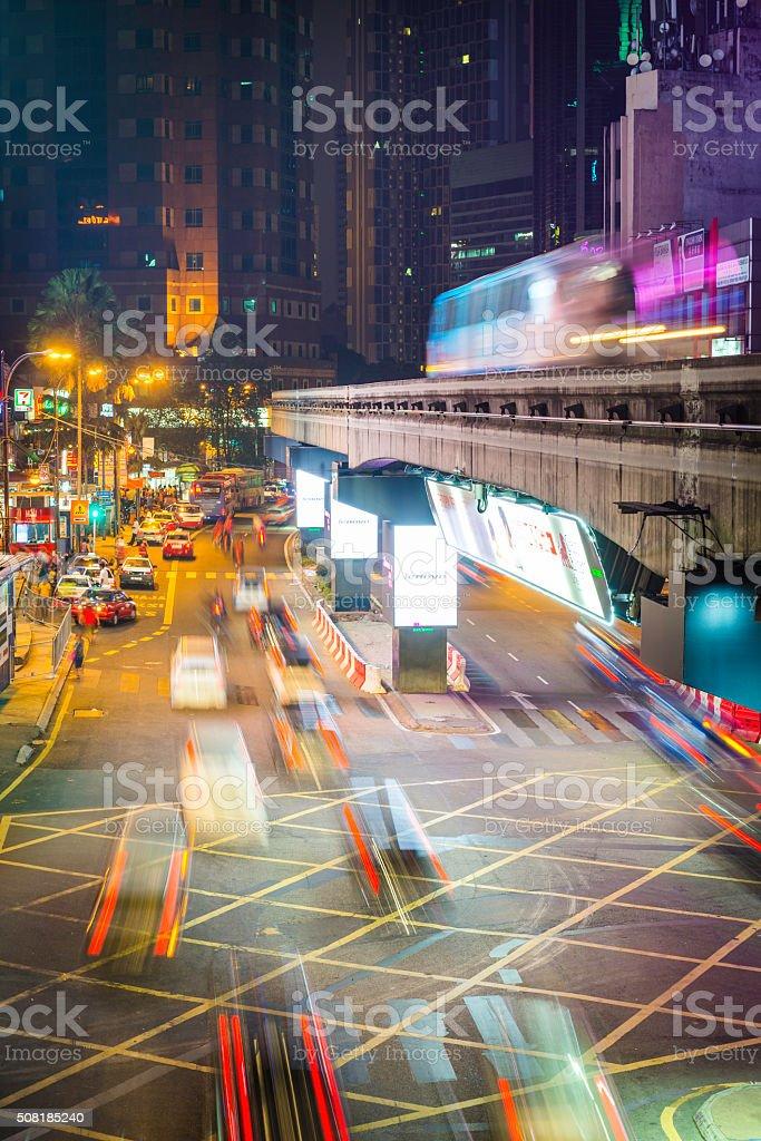 Monorail traffic zooming through busy neon night city Kuala Lumpur stock photo