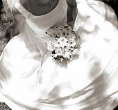 A monotone photo from above of a bride in her wedding dress