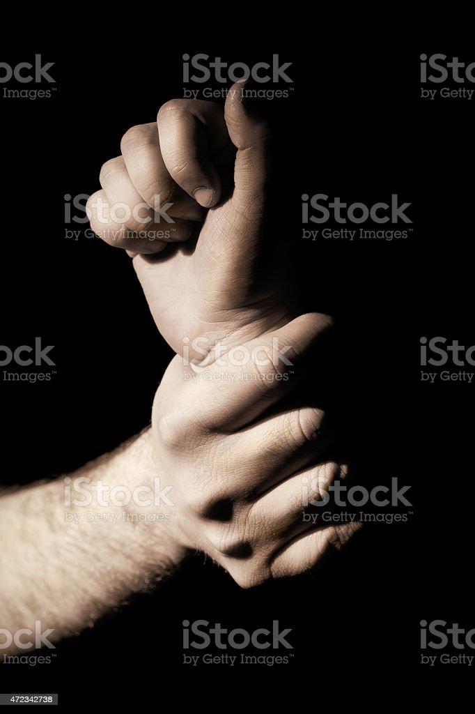 Monotone photo of a hand grabbing someone's wrist stock photo