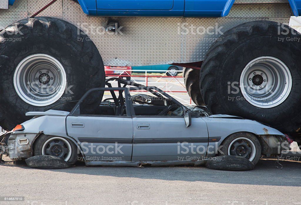 Monster truck wrecked car on road stock photo